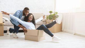 Man pushing happy woman in moving box