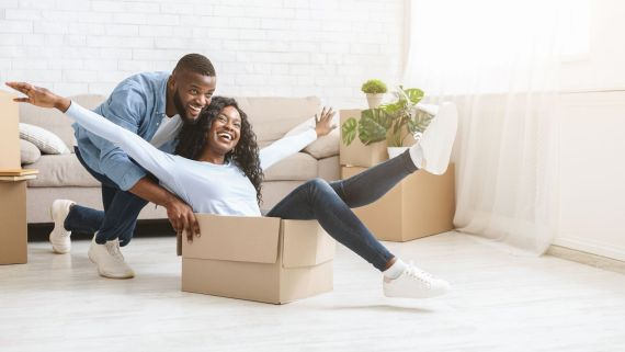 Man pushing happy woman in moving box