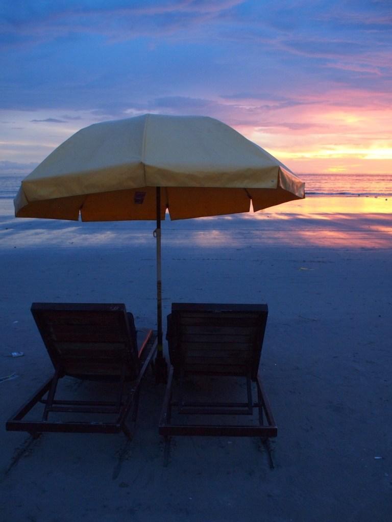 strandstoelen bij zonsondergang Pentai Cenang