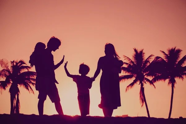 A family walking along the beach during sunset
