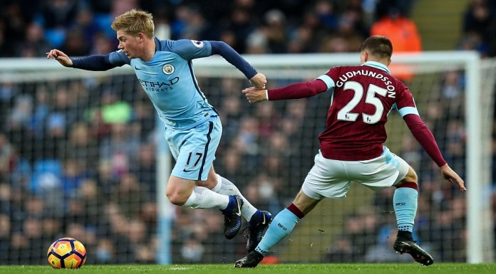 Manchester City playmaker Kevin De Bruyne (left) skips past Gudmundsson as he tries to start an attack for his side