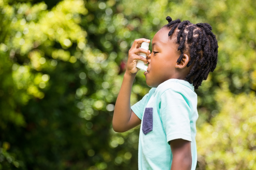 little boy using inhaler due to summer asthma