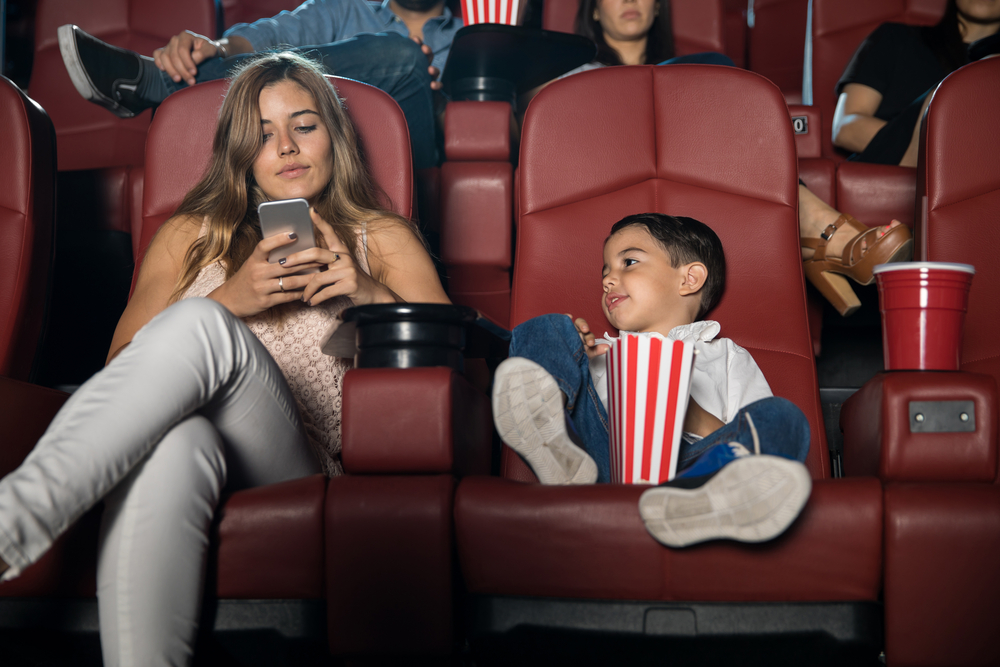 mom ignoring child while on her phone in theater
