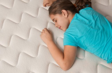 Little girl lying down on her new comfortable mattress