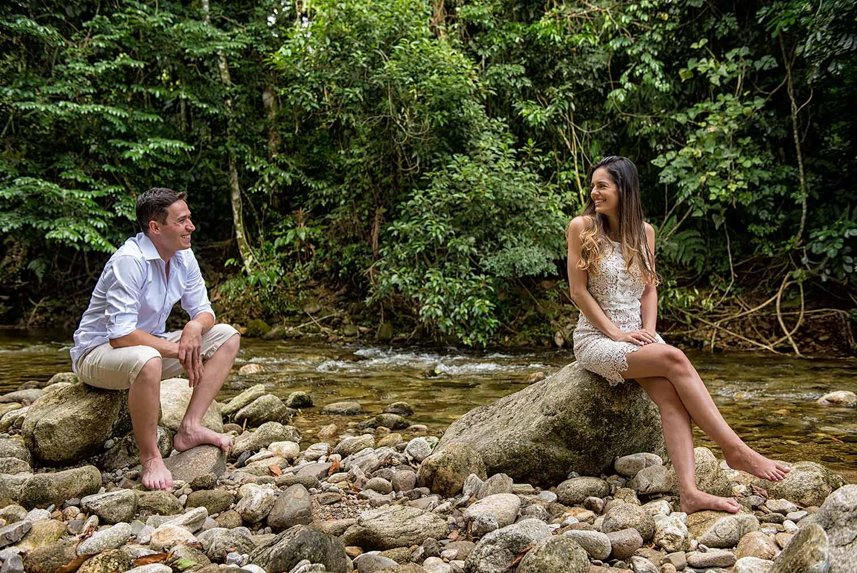 Ensaio prewedding na natureza noivos sentados em pedra na se olhando com o rio raso e transparente ao seus pés