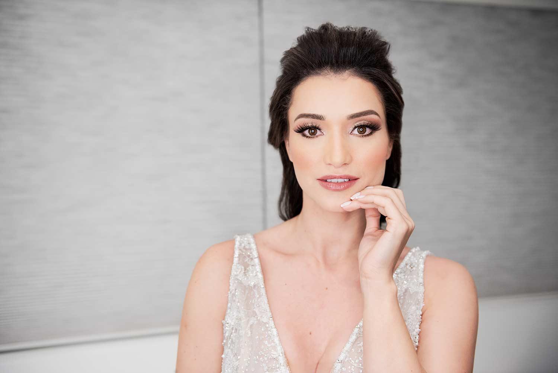 Noiva faz pose de moda olha para a câmera com a mão próxima do rosto em gesto sutil no salão di biagi