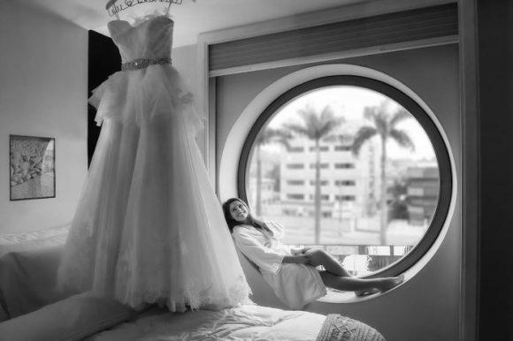 foto artística da noiva sentada na janela de seu quarto no hotel unique olhando seu grandioso vestido pendurado