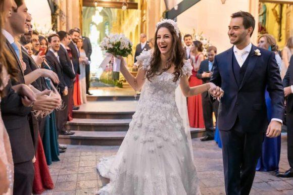 Foto fantástica de noiva feliz saindo da igreja após casar de mãos dadas com o noivo e padrinhos do lado