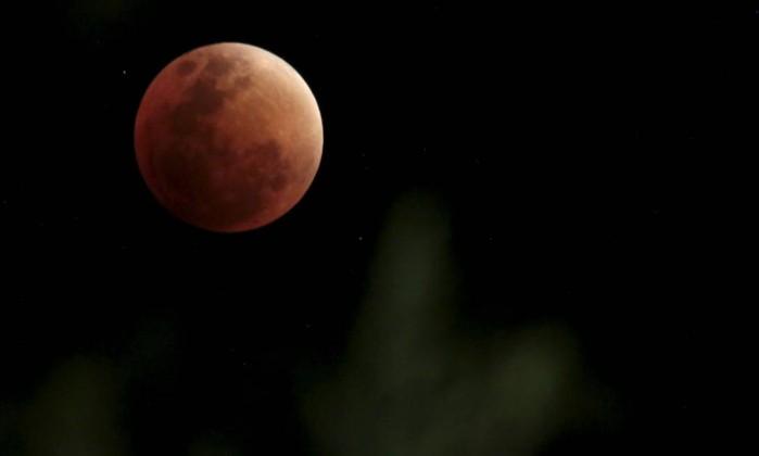 A lua, na cor vermelha escura, é coberta pela sombra da Terra durante eclipse lunar total em La Paz - DAVID MERCADO / REUTERS