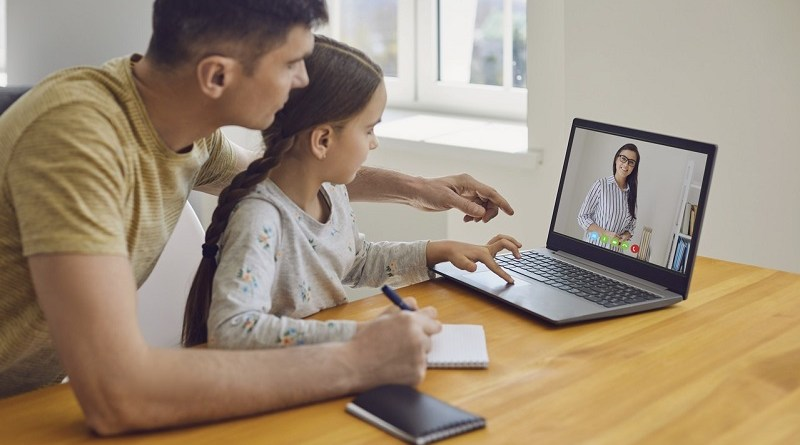 Online learning lessons education school. Father and daughter are doing online education with a teacher using a laptop sitting at a desk at home.