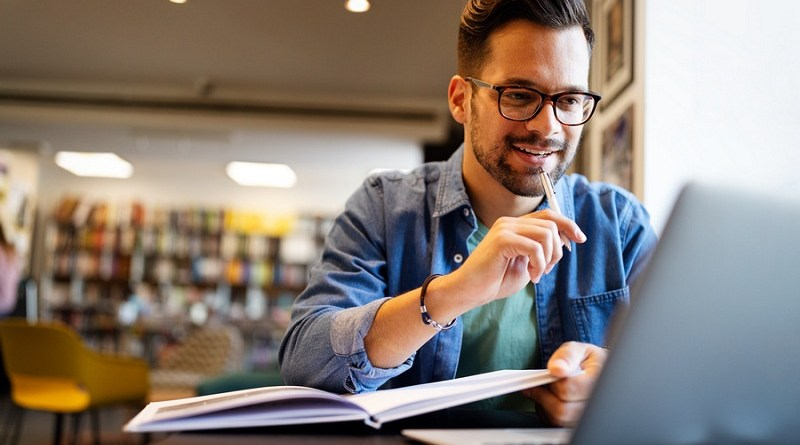 Smiling male student working and learning in a library