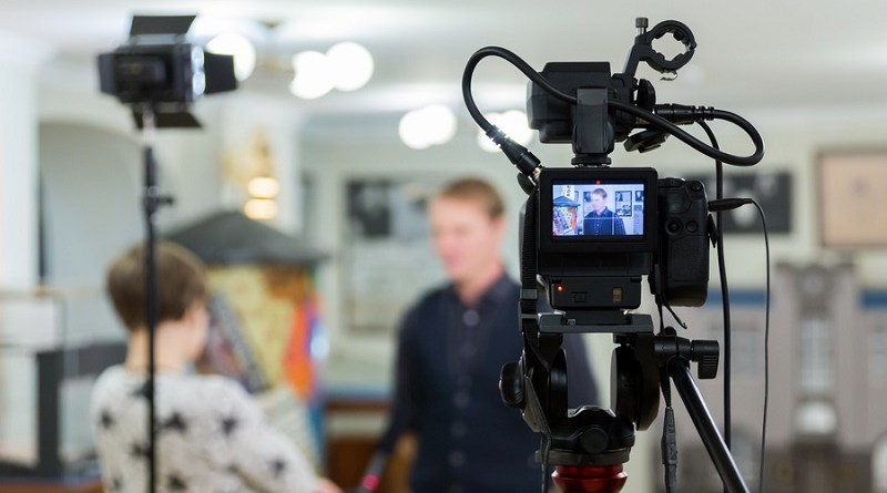 Video of the interview. Television equipment, camcorder with LCD screen, lighting equipment.