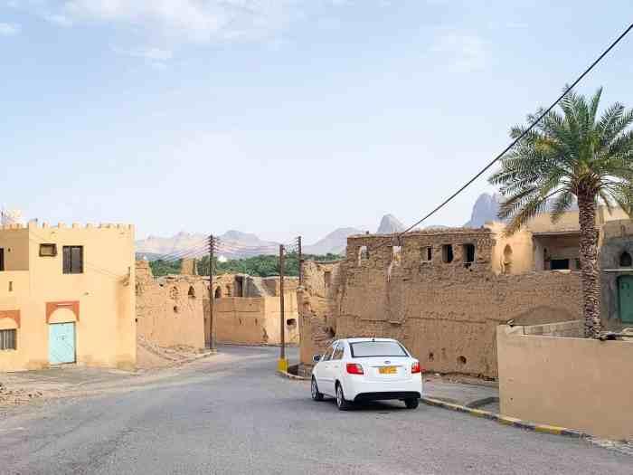 car at the entrance to the Al Hamra ruins in Oman