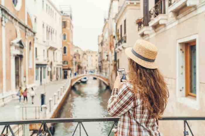 woman charging phone with portable charger on Italy packing list