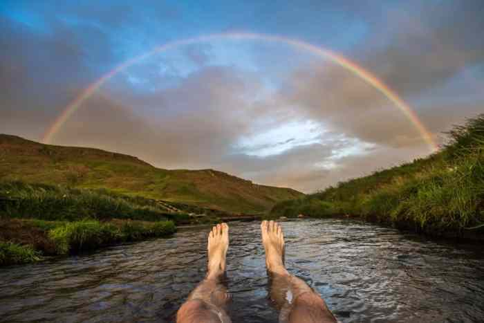 person looking at rainbow while bathing at Reykjadalur Hot Springs