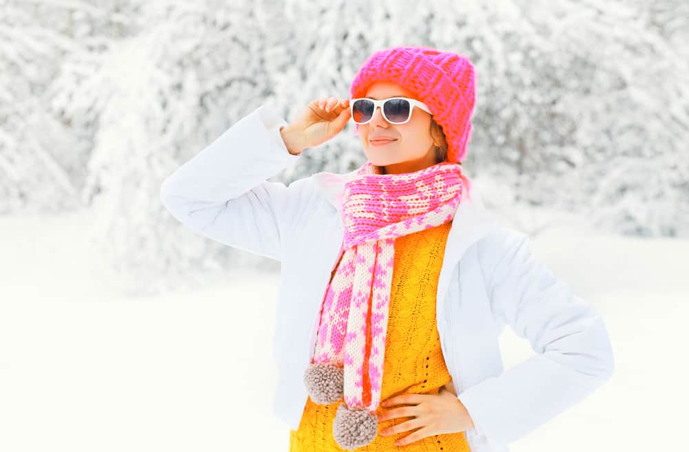 girl wearing sunglasses from her winter packing list