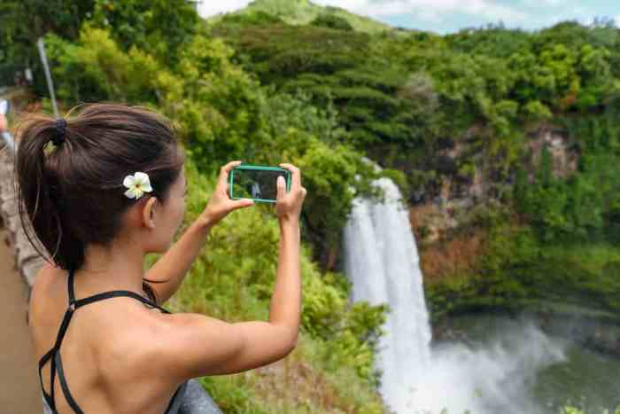 Don't forget a phone charger when planning your Hawaii packing list so you can take photos of waterfalls like this woman is!