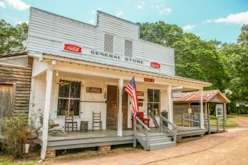 White and wooden general store with fron porch and USA flag