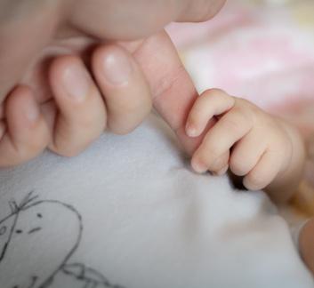 Photo de la main d'un bébé qui tient l'index de son père