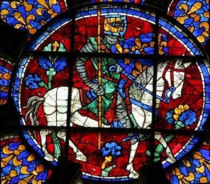 Fig. 6. Chartres, cattedrale Notre-Dame, rosone (ca. 1215-1216). Il principe Luigi (il futuro Luigi VIII) in grande tenuta araldica, porta uno scudo di Francia antica. Si tratta del più antico esemplare smaltato dell'arma dei capetingi.
