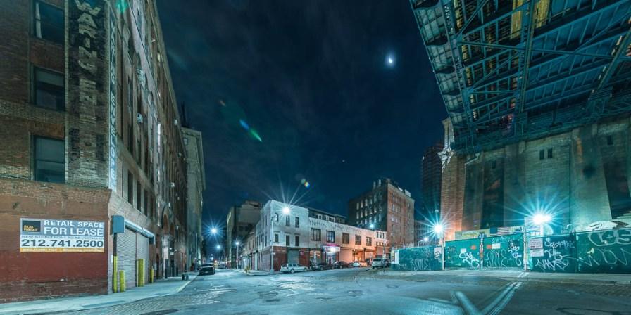 Straßenszene bei Nacht unterhalb der Manhattan Bridge.