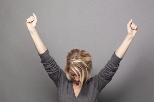 a woman wearing grey blouse raising her arms upwards with closed fist in a slightly light grey background, menstrual cycle