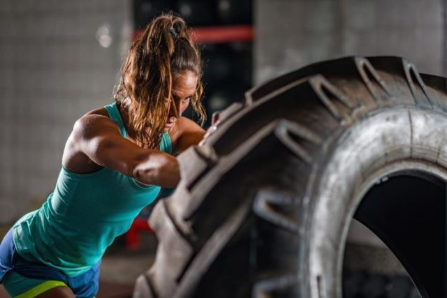 female working out with a huge tire, mentrual cycle