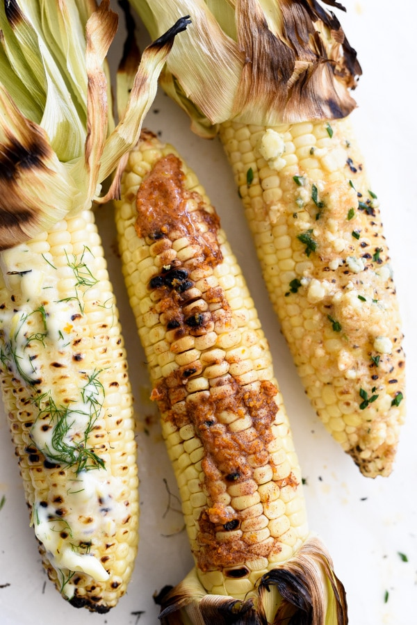 three ears of grilled corn slathered with compound butter