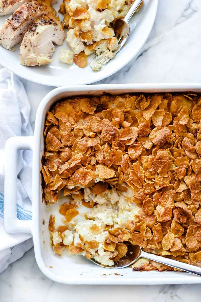 hash brown potato casserole with cornflakes in white baking dish