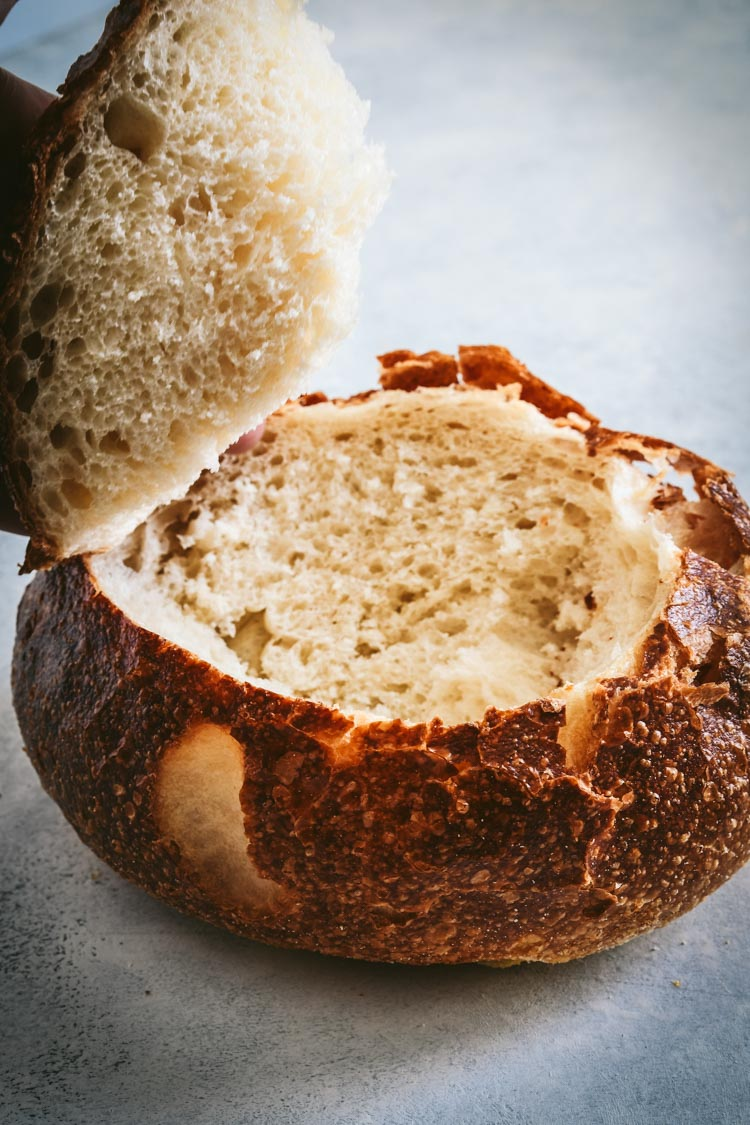 Sourdough round cut into a bread bowl for spinach dip