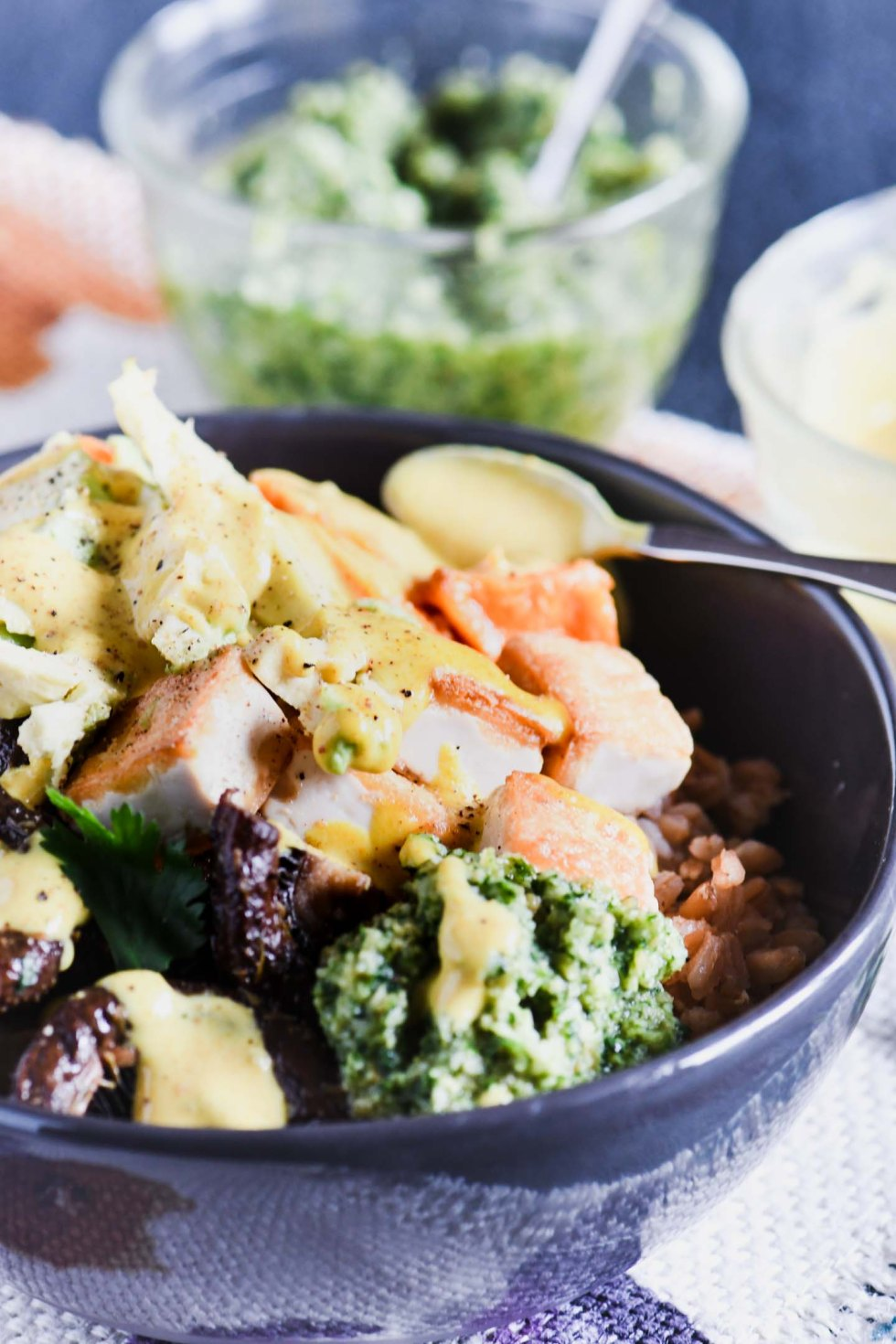 This buddha bowl starts with a base of ancient grains and gets topped with tofu, sweet potatoes, miso sauce and cilantro pesto for a healthy vegetarian meal!