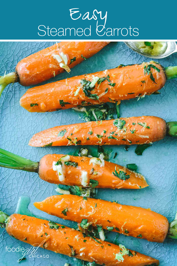 Bright orange steamed carrots on a teal dish