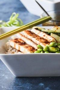 Crispy tofu rice bowl topped with bok choy, edamame and teriyaki glaze