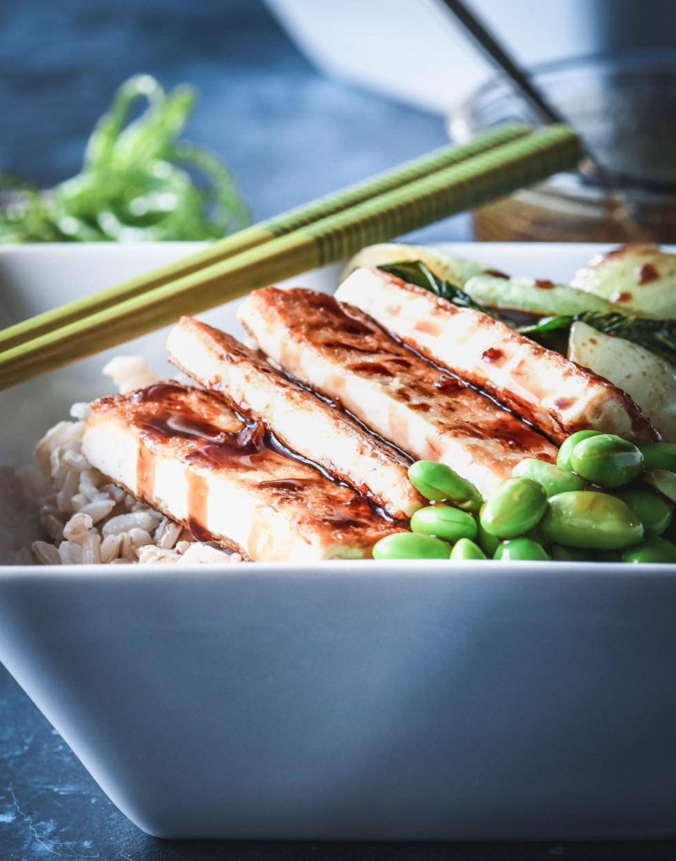 Crispy tofu rice bowl topped with bok choy and edamame then drizzled with teriyaki glaze.