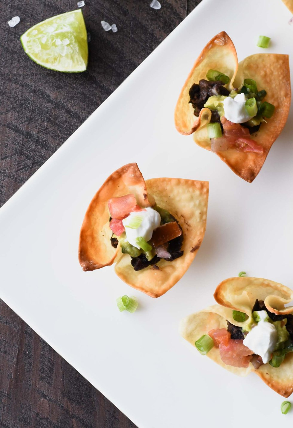 Wonton taco cups from overhead filled with seasoned black beans and topped with guacamole, pico de gallo and cilantro lime sauce