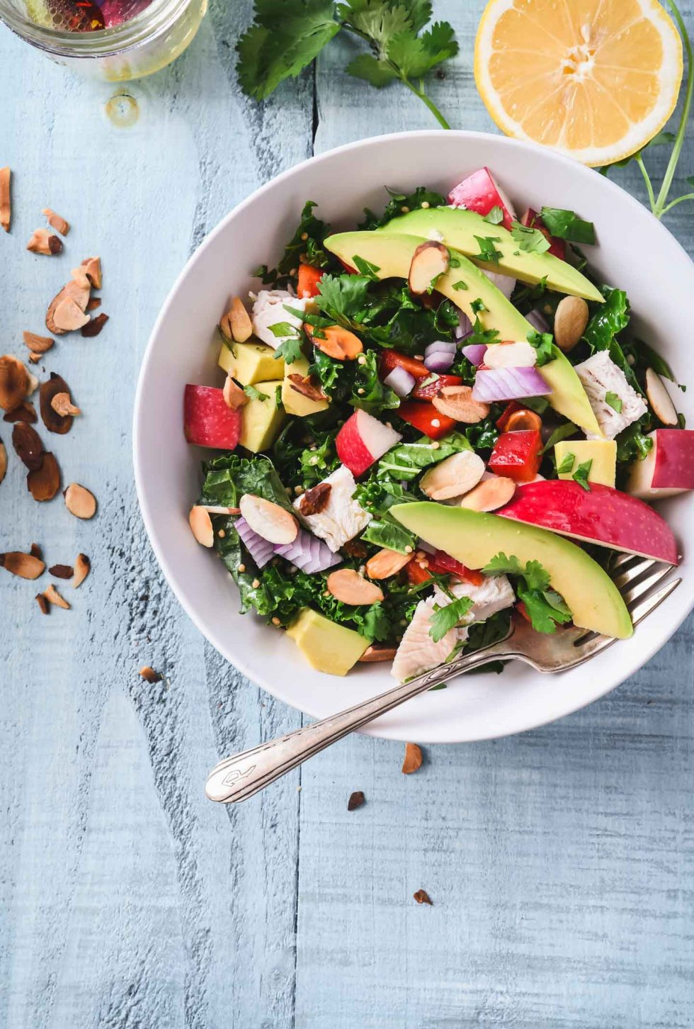 Chopped Kale Salad topped with bright veggies in an off-white bowl