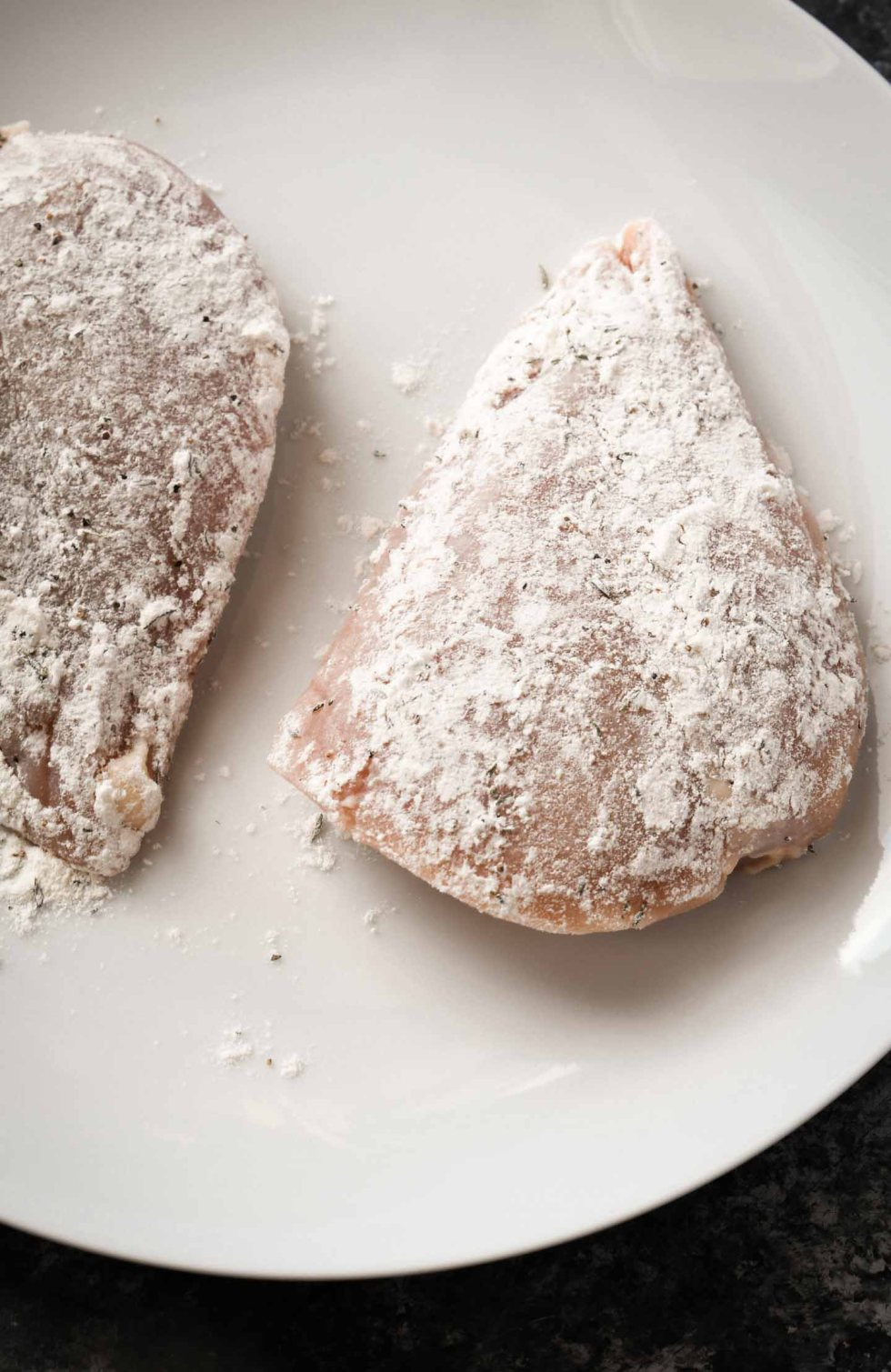 Floured chicken breasts on a white plate