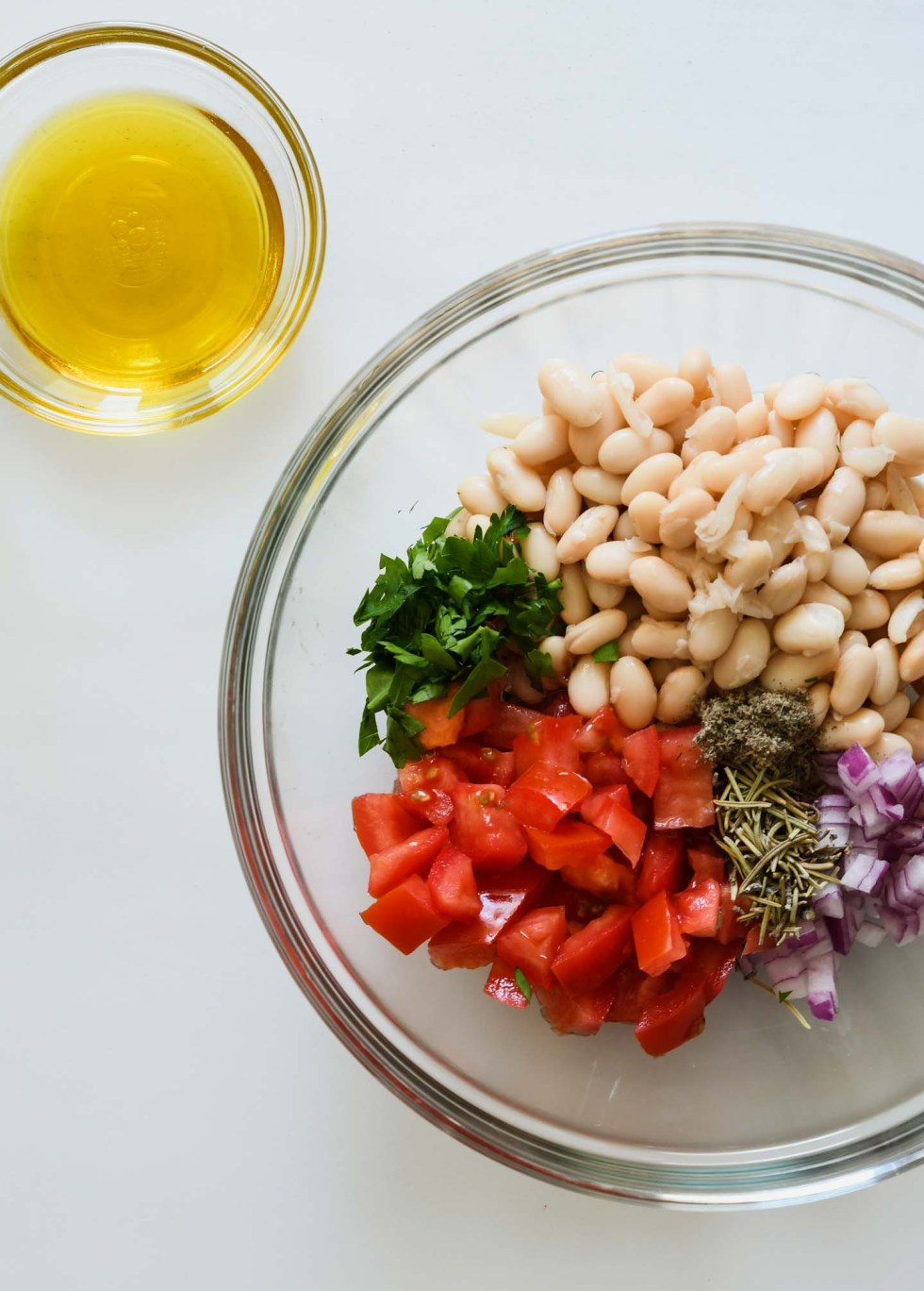 White beans, chopped tomato, red onion and spices in a clear glass bowl