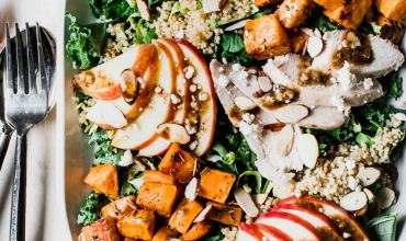 Chopped kale salad topped with sweet potatoes, apples, quinoa and goat cheese