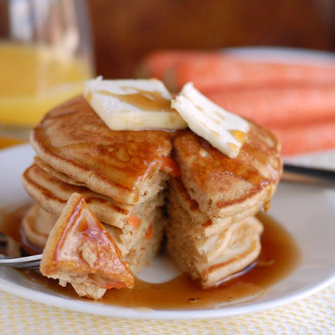 Stack of pancakes with syrup and butter on top.
