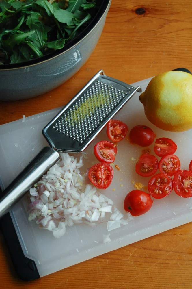 Bowl of arugala, lemon zest, diced tomatoes and shallots on a cutting board