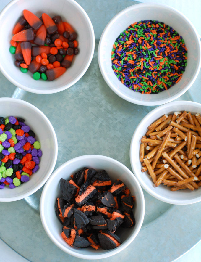 Halloween Candy Bark is easy and fun to make! Use your favorite candies and sprinkles to make this festive treat.