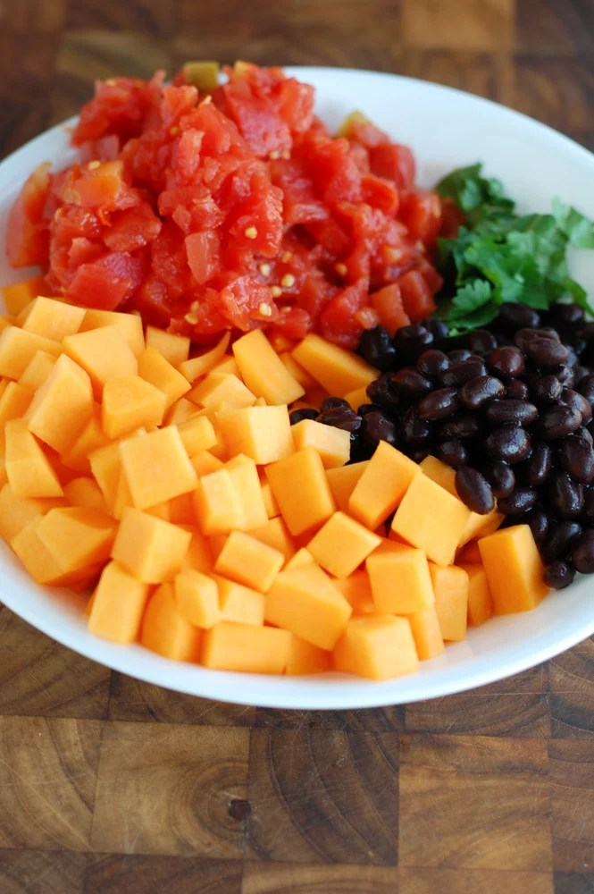 bowl with diced butternut squash, rotel tomatoes, black beans and cilantro