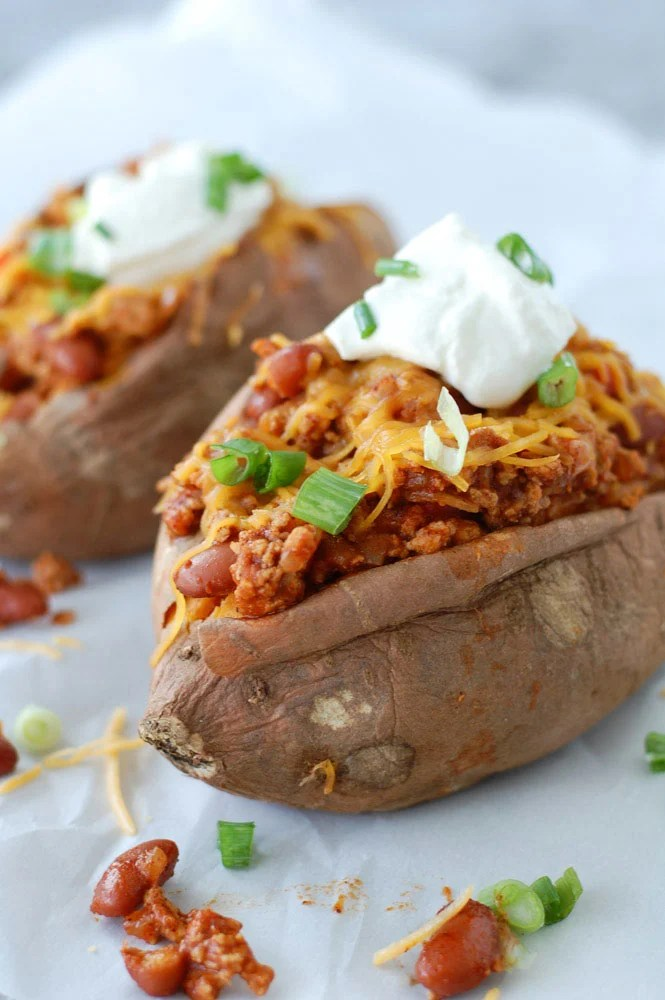 Fast and flavorful turkey chili smothered sweet potatoes with cheese and sour cream on top. The perfect healthy and hearty week night meal.
