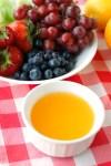 Bowl of orange dip and bowl of fruit.