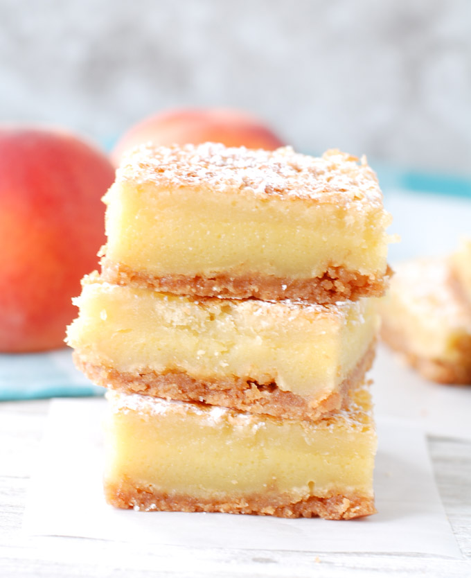Peach Nectar Custard Bars with Vanilla Wafer Crust start with a crushed vanilla wafer crust, topped with a custard like filling, sugar crust top and dusted with powdered sugar.