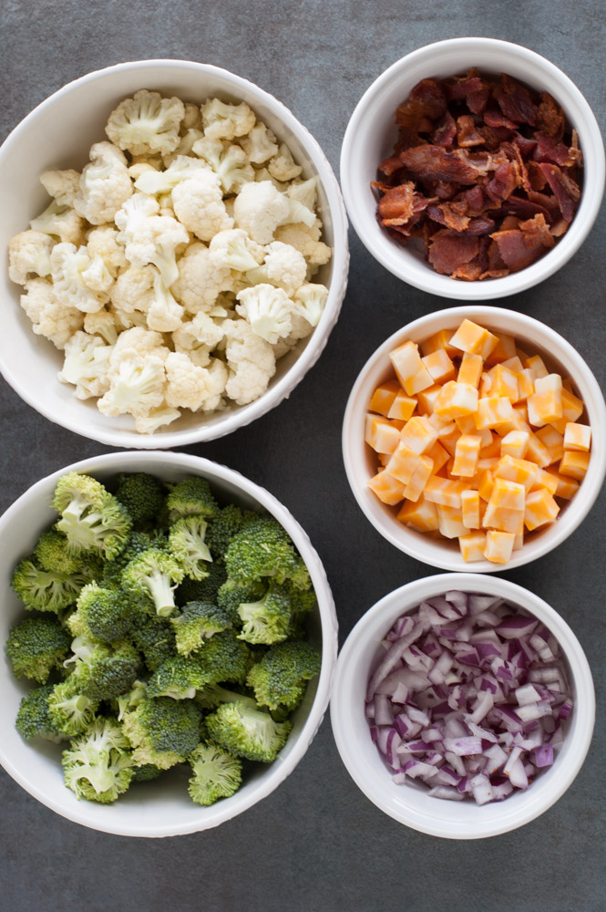 Bowl of broccoli, cauliflower, bacon, cheese cubes and red onion