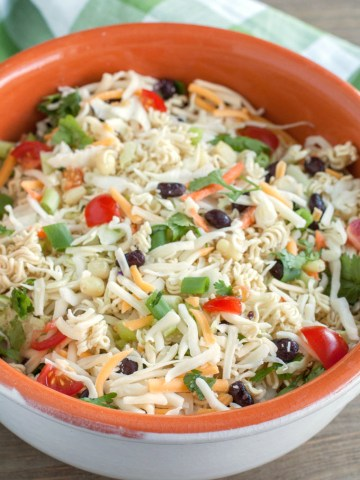 Large bowl of salad with olives, tomatoes and cheese.