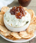 Bowl of whipped goat cheese topped with fig jam.
