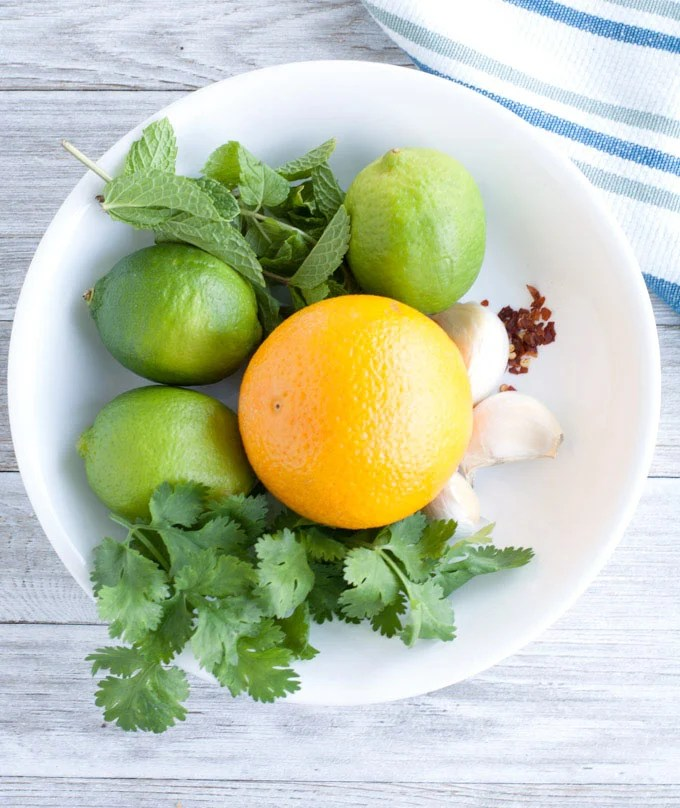 Bowl with orange, mint, cilantro, lime and garlic